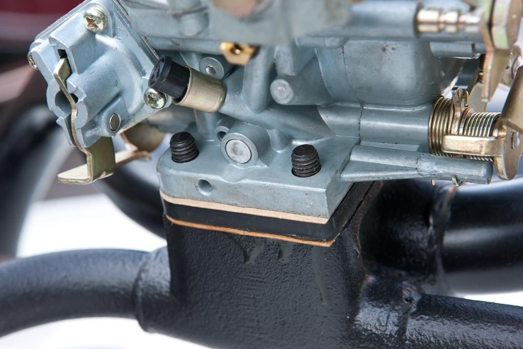 un carburatore appoggiato su un collettore con le guarnizioni correttamente posizionate sopra e sotto al distanziale.