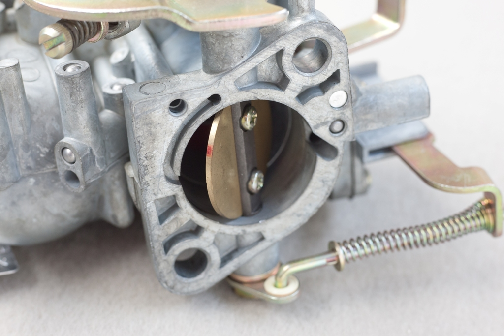 La farfalla di un carburatore monocorpo semiaperta, vista dal lato del collettore di aspirazione.
